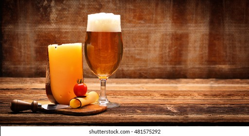 Yellow cheese appetizer and beer on brown vintage background