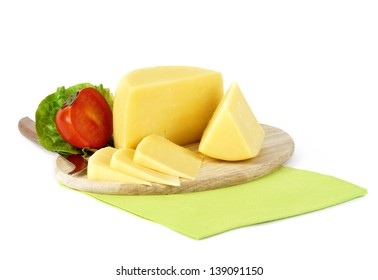 yellow cheese cut in pieces on a wooden plate