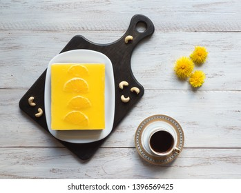 Yellow cheesecake with oranges and cup of coffee white wooden table. Top view.
