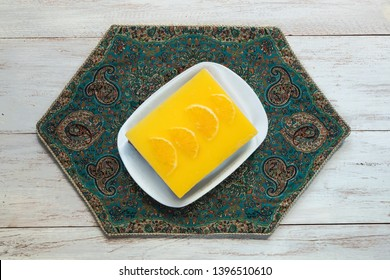 Yellow cheesecake with oranges on a white wooden table. Top view.