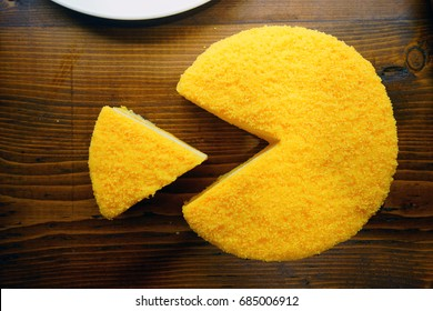 A yellow cheesecake wheel shaped as pacman