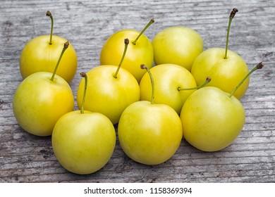 yellow Cherry plum (Prunus cerasifera). ripe of fruit on woody table