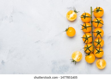 Yellow cherry tomatoes on branch, whole on cut in half, on rustic table top view with copy space.