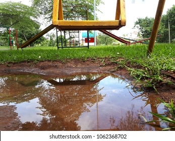 a yellow child swing in a park with some call of flooded land reflecting the sky and trees that are around a Beautiful Green Lawn and some other background toys