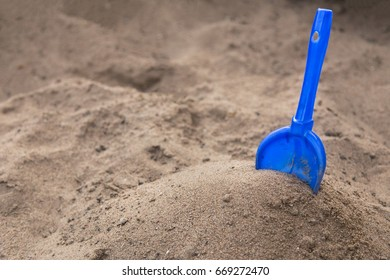 Yellow children's shovel in the sandbox close up