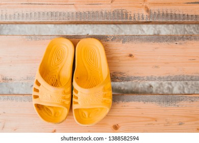 Yellow children's street Slippers on wooden bench top view.