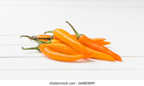 Yellow chili pepper on white table background