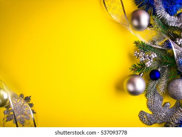 Yellow Christmas background with fir tree, toys and bows