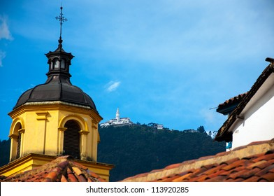 A yellow church in Bogota with Monserrate in the background.