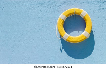 Yellow circular lifebuoy hanging on blue wall with copy space