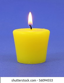 Yellow citronella candle that is lit on a blue background