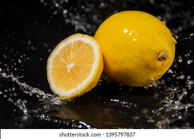 """Yellow citrus fruit """"Citrus limon"""", the fruit of the tree lemons on a black wooden background in the water. Close-up, splash of water drops. Slow motion."""