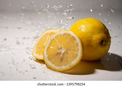 """Yellow citrus fruit """"Citrus limon"""", the fruit of the tree lemons on a white, gray background in the water. Close-up, splash of water drops. Slow motion."""