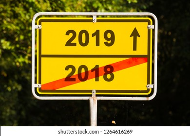 yellow city-limit sign and the words 2018 and 2019 in front of green vegetation, business concept for turn of the year