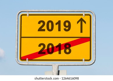 yellow city-limit sign and the words 2019 and 2018 in front of the blue sky, business concept for turn of the year