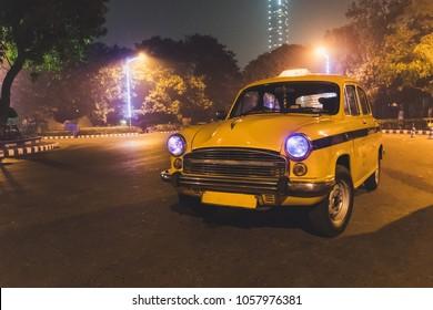 Yellow classic taxi service at Kolkata airport parking at night
