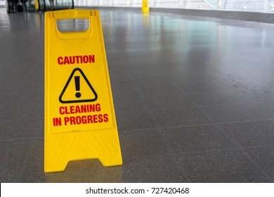 A yellow cleaning in process sign on the floor