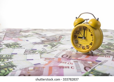 Yellow clock and money on the table.