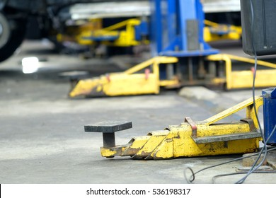 Yellow close up lift's arms in a car repair station