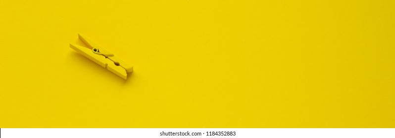 Yellow clothespin on the background, space for text, close-up