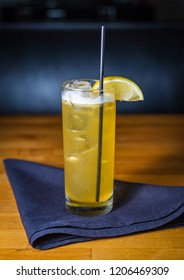 A yellow cocktail with a lemon garnish on a blue cloth napkin on an orange & brown wooden table.
