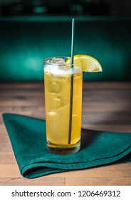 A yellow cocktail with a lemon garnish on a green cloth napkin on a brown wooden table.
