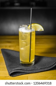 A yellow cocktail with a lemon garnish on a black cloth napkin on a wooden table.