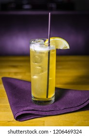 A yellow cocktail with a lemon garnish on a purple cloth napkin on a wooden table.
