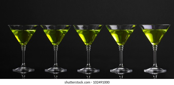 Yellow cocktail in martini glasses isolated on black