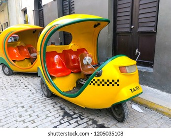 Yellow Coco taxi's in Old Havana, Cuba. Classic and old model sightseeing taxis. Coco taxi is an auto rickshaw type taxi vehicle and a cheap way to go from one point to the other 10/02/2018