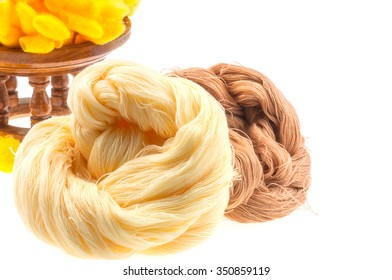 Yellow cocoon and yarn over white background
