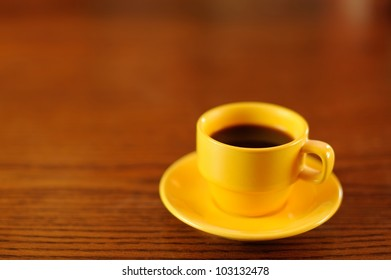 Yellow Coffee Cup on Wooden Table. Yellow demitasse coffee cup and saucer on a wooden table. Shallow DOF. Space for copy.