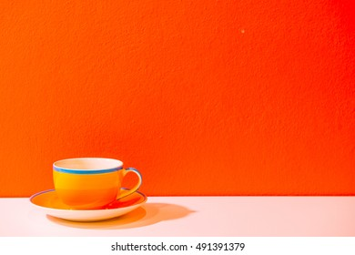 Yellow coffee cup with orange wall, Thailand.
