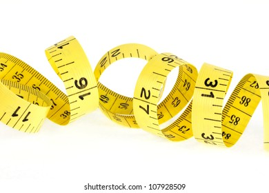 Yellow coiled tape measure on a white background