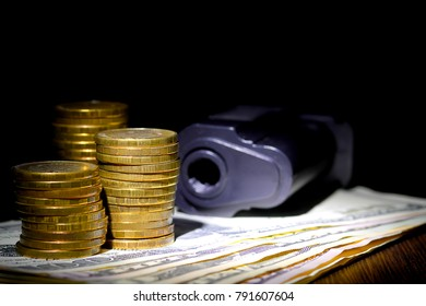 yellow coins, dollar banknotes and a pistol under flashlight in darkness, closeup, criminal money concept