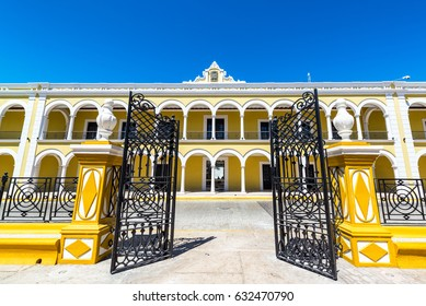 Yellow colonial building and gate as seen from the main plaza in Campeche, Mexico