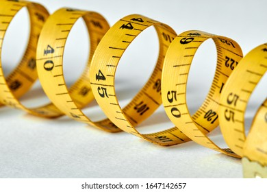 Yellow color centimeter with black figures for measurement of length and width on a white background. Measuring tape of the tailor for you design. Closeup, selective focus