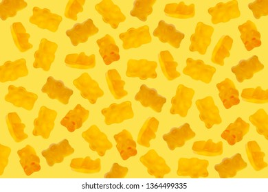 Yellow color jelly candy gummy bears on yellow background. Falling gummy bear