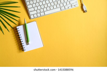 Yellow color office desk, top view with keyboard, cable, pen, memo pad and green plant with copy space