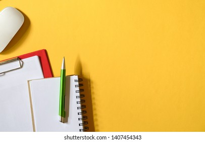 Yellow color office table top view with mouse, clipboards with paper, memo pad and pen. Copy space