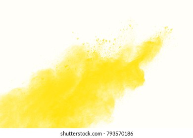 Yellow color powder explosion cloud isolated on white background.Closeup of yellow dust particles splash isolated on  background.