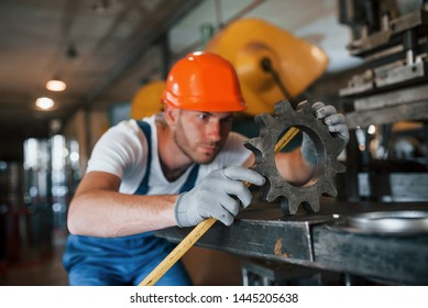 Yellow colored measuring tape. Man in uniform works on the production. Industrial modern technology.