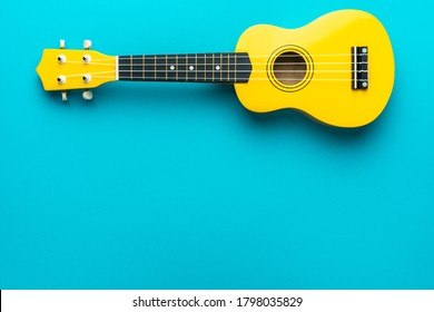 Yellow colored wooden ukulele guitar on the turquoise blue background. Overhead photo of ukulele with copy space.