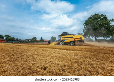 A yellow combine harvests wheat on a field in germany
