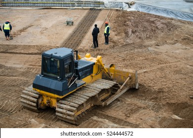 Yellow Construction bulldozer at Work in the pit, preparing the foundation for a multi-storey building