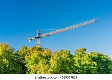 Yellow construction crane behind green trees