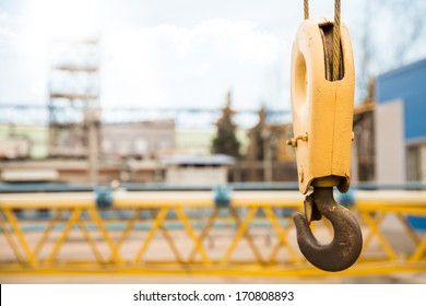 yellow construction crane hook with some industrial buildings on the background