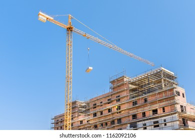 yellow construction crane lifts an object to a building under construction and unrecognisable worker in safety wear wathes from scafolding on the incomplete brick building against a blue summer sky