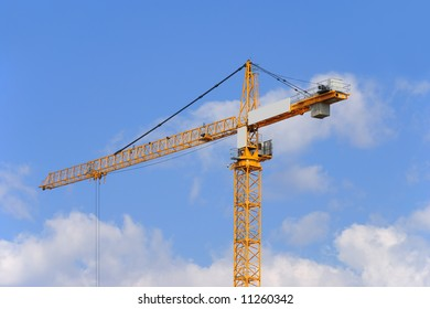 Yellow construction crane on a sky background