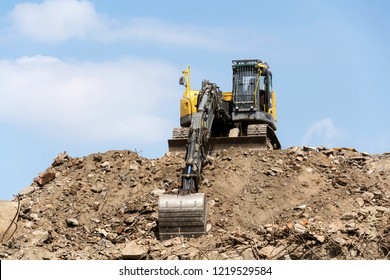 Yellow construction digger, excavator on demolition site stand on debris, sunny day clear blue sky